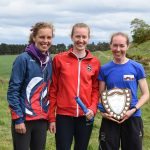 Three female orienteers with trophy at Scottish Orienteering Championships in the Scottish Countryside