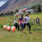 Trio of fast orienteering finishing race near Braemar in Scottish Highlands as part of a group activity